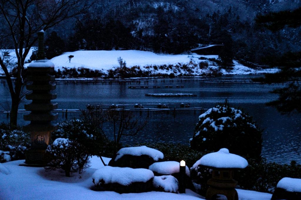 夕暮れの日本庭園、趣のある雪景色の写真