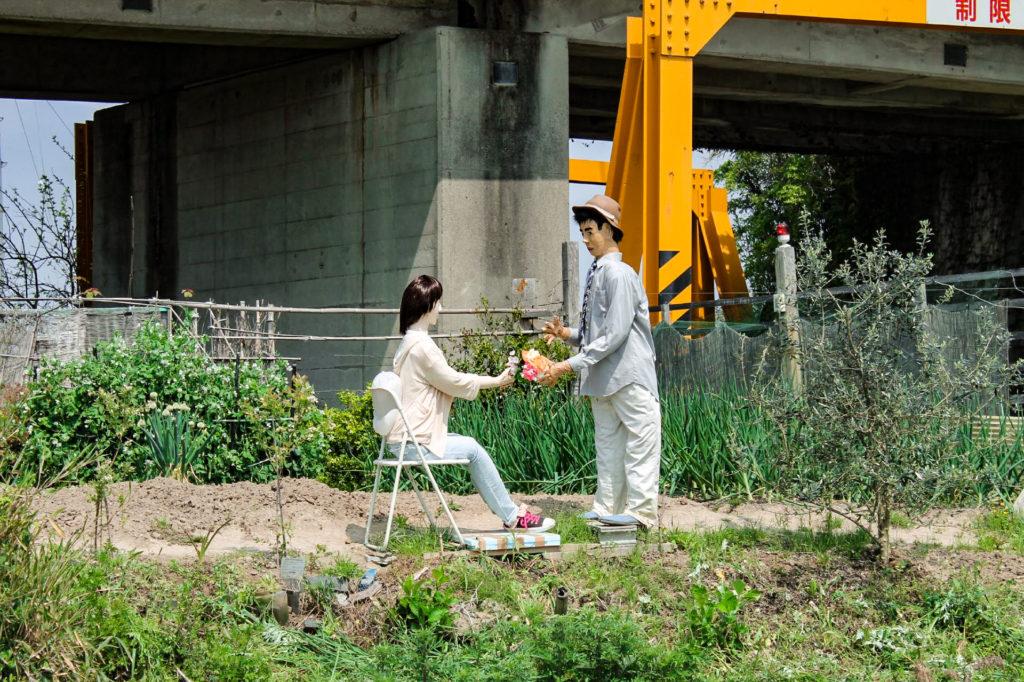 花束を渡す案山子(かかし)の写真