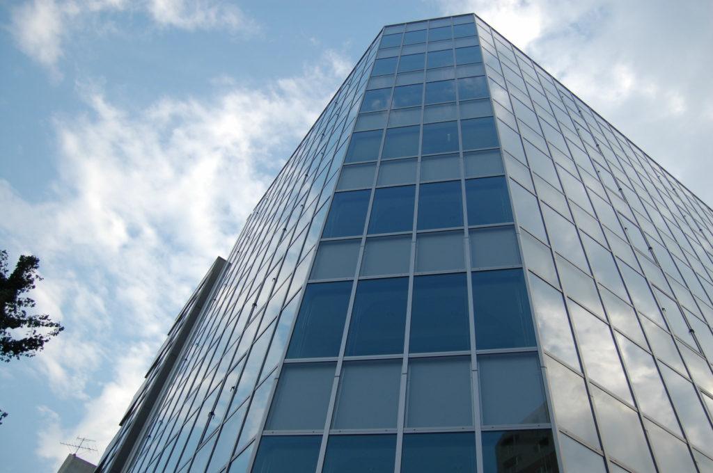 オフィスビルとガラス窓に映る雲