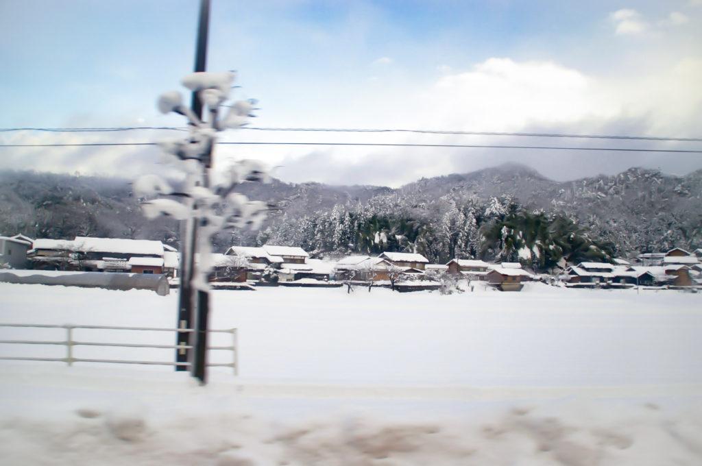 車窓から見える雪で真っ白な田舎