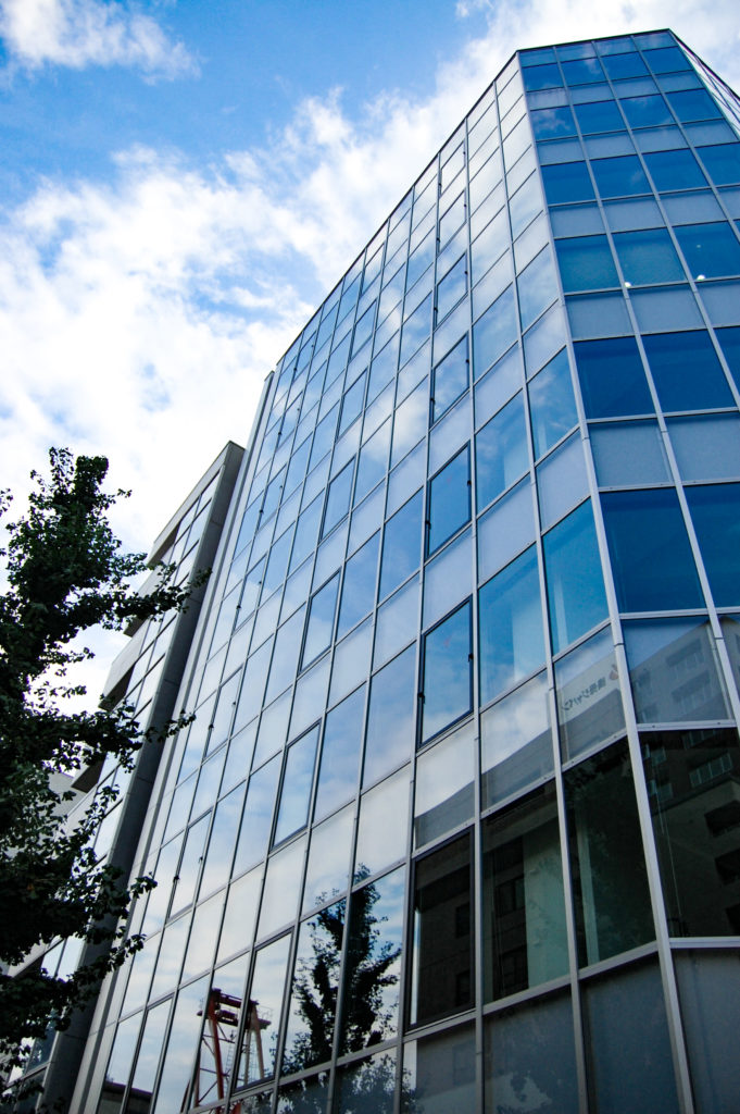 オフィスビルとガラスに映る青空