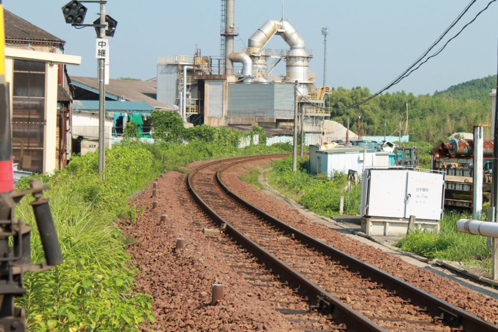ローカル線の先に見える工場