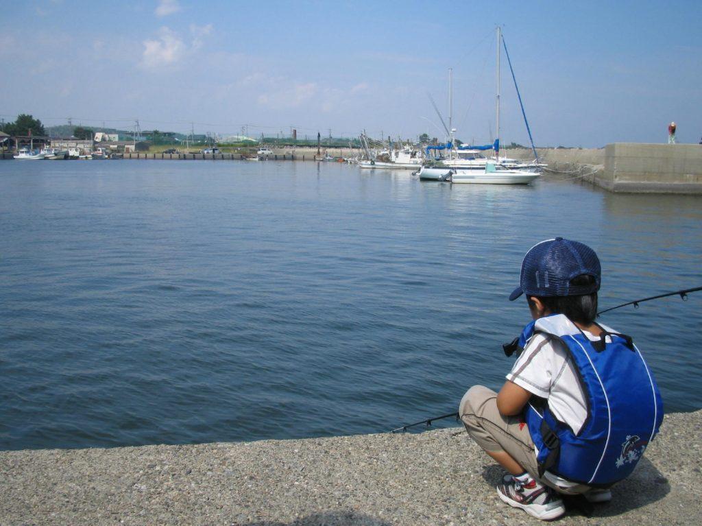 釣竿を持って海を眺める子ども