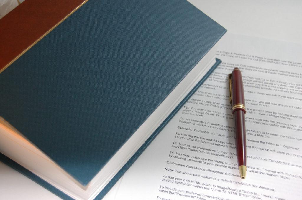 分厚い本と赤いボールペン