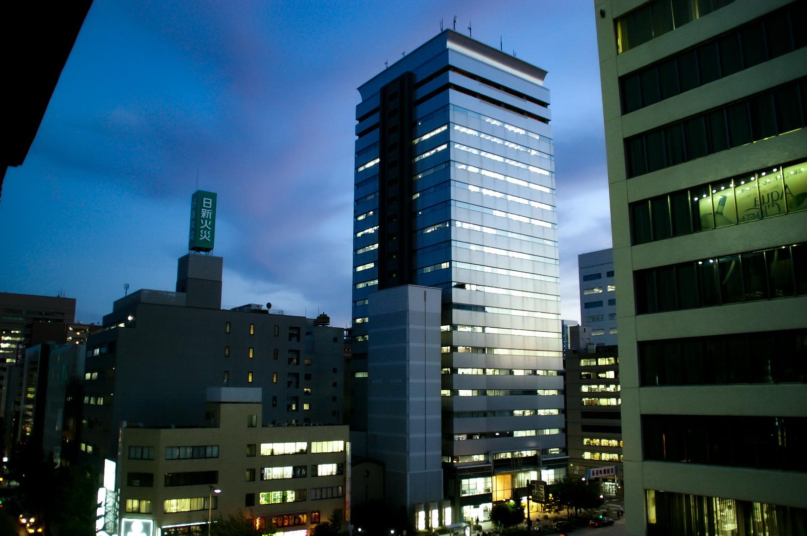 徐々に夜を迎える夕暮れのオフィスビル