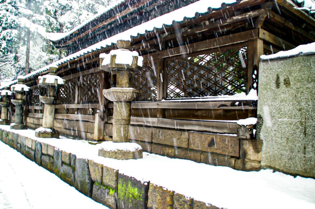 神社の灯篭と屋根に積もる雪