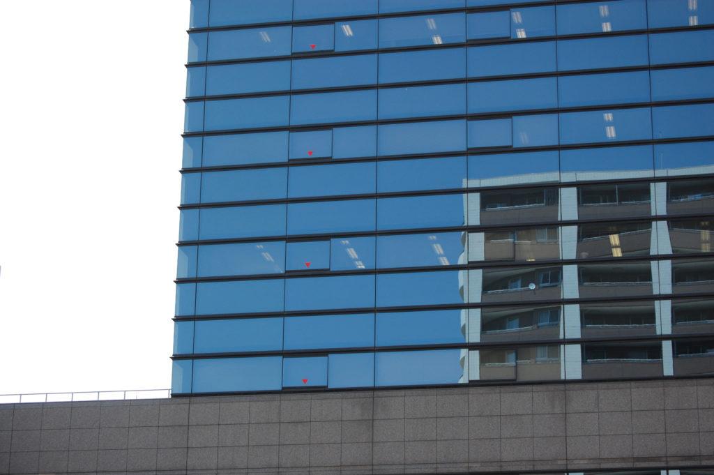 鏡のように反射するオフィスビルのガラス窓