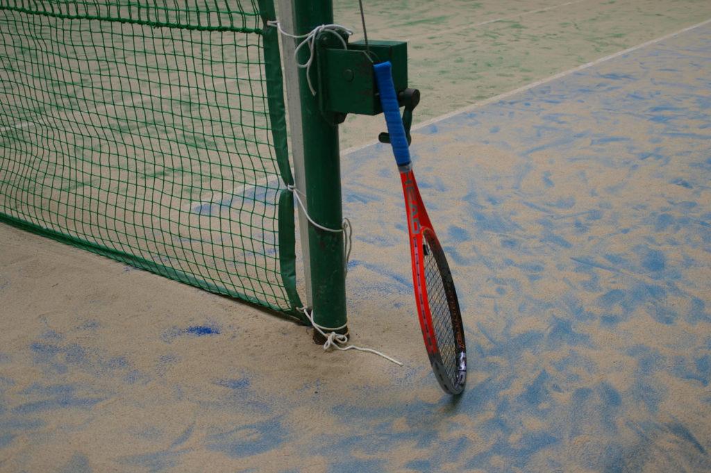 ネットに立てかけたテニスラケット