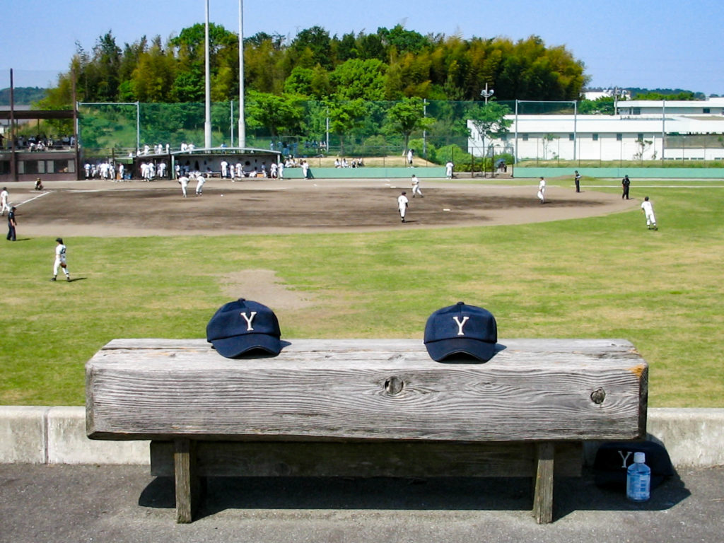 ベンチに置かれた2つの野球帽の写真