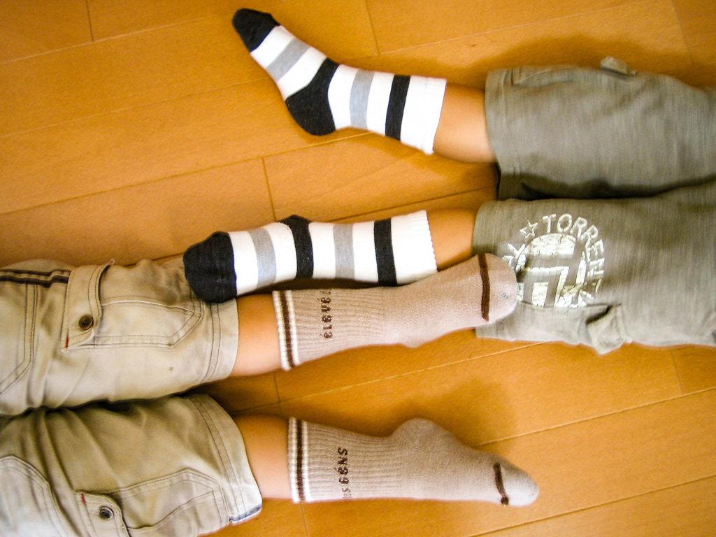 双子の子供が寝そべった時の足の写真
